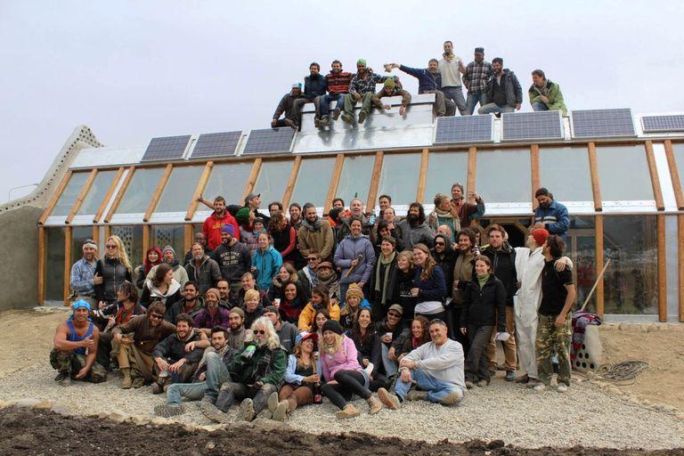 Los voluntarios que participaron de la academia y, detrás, la Earth Ship terminada