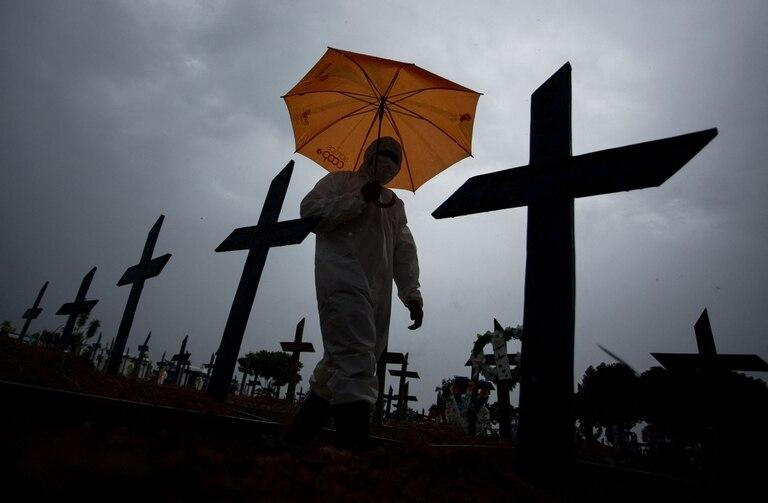 Trabajadores con protección especial caminan junto a tumbas de víctimas del Covid en el cementerio Nossa Senhora Aparecida de Manaos