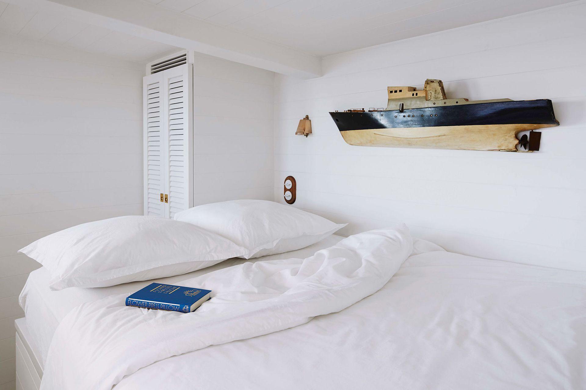 Este dormitorio, como el resto del espacio, fue revestido con madera pintada de blanco para una sensación de pulcritud general y también de desahogo a pesar de lo bajo del cielo raso.