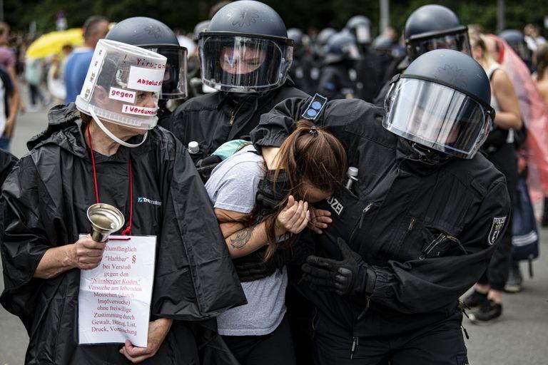 Agentes de la policía arrestan a una manifestante durante una protesta en Berlín, el domingo 1 de agosto de 2021. (Fabian Sommer/dpa vía AP)