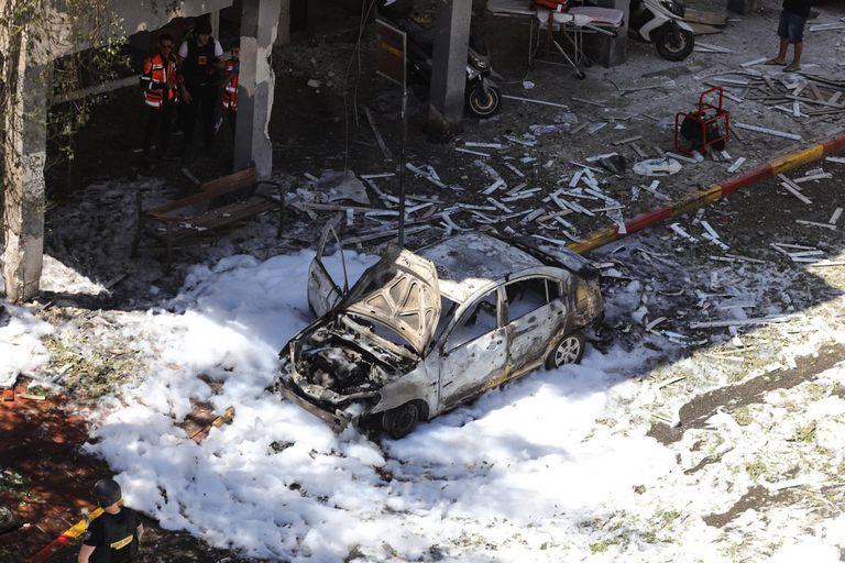 Un automóvil quemado frente a una casa dañada que fue alcanzada por un cohete disparado por el movimiento islamista palestino Hamas desde Gaza hacia Israel