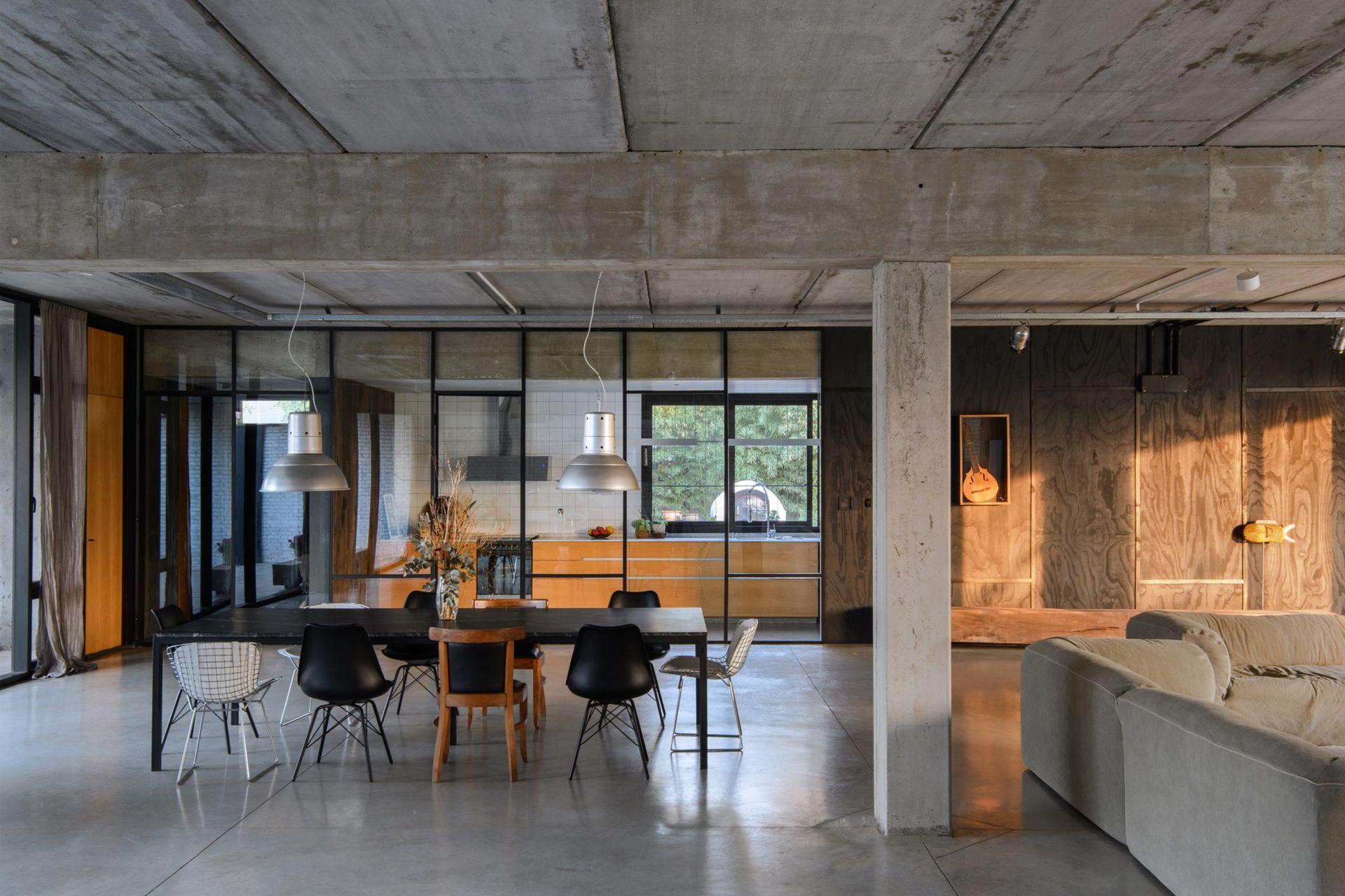 """Lámparas galponeras que habían usado en el estudio de arquitectura; mesa con tapa de mármol 'Ebony Crystal' montada sobre una estructura de caño pintado (Estudio Benito). Las sillas, """"una de cada pueblo"""" para desestructurar."""
