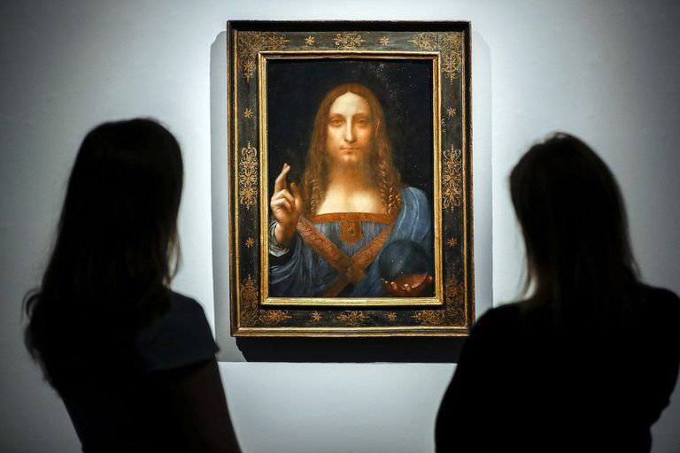 Christies employees pose in front of a painting entitled Salvator Mundi by Italian polymath Leonardo da Vinci at a photocall at Christies auction house in central London on October 22, 2017 ahead of its sale at Christies New York on November 15, 2017. Salvator Mundi, one of fewer than 20 known paint