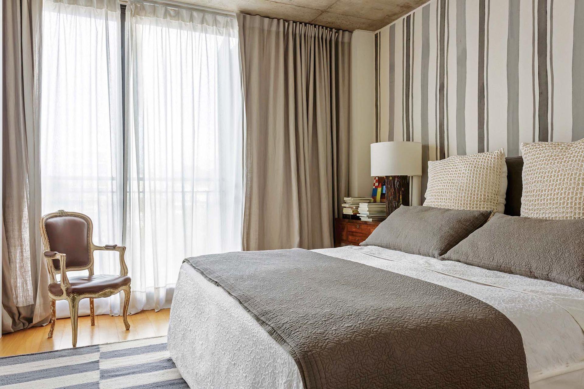 Un doble cortinado –voile translúcido detrás y lino por delante– y un género pintado a mano en la pared de la cabecera marcan el cálido tono del cuarto principal.