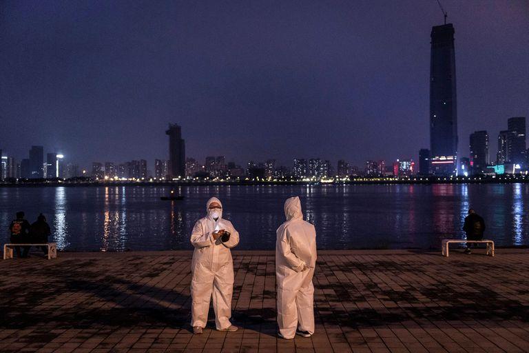Dos personas con trajes protectores mientras visitan Hankou Beach Park en Wuhan, en la provincia central de Hubei, en China