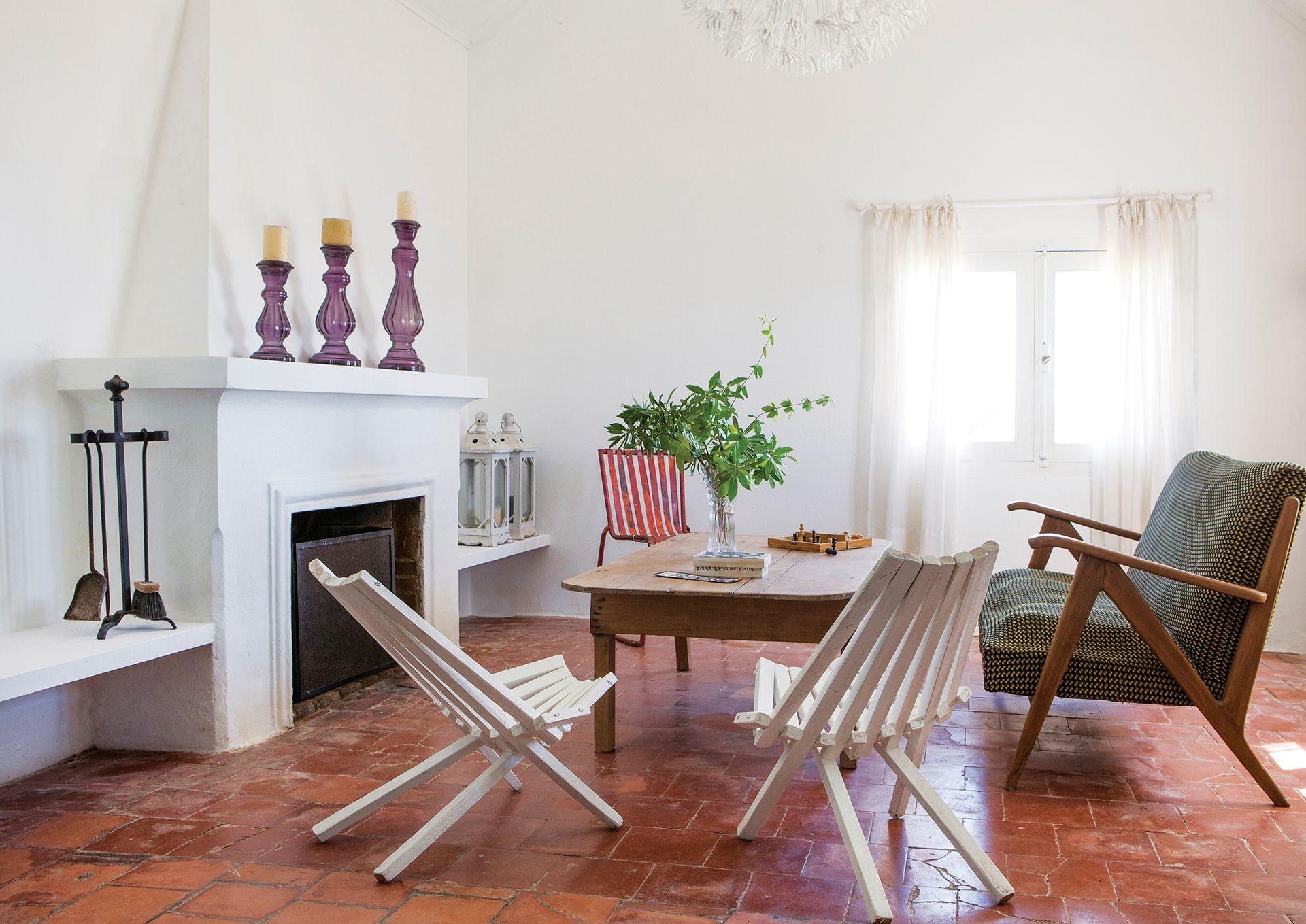En el living, cerámicos terracota organizado en torno al hogar y mirando a la Rambla. Además, mesita de lapacho, sillas franciscanas pintadas de blanco y un sillón vintage de estilo nórdico con apoyabrazos.