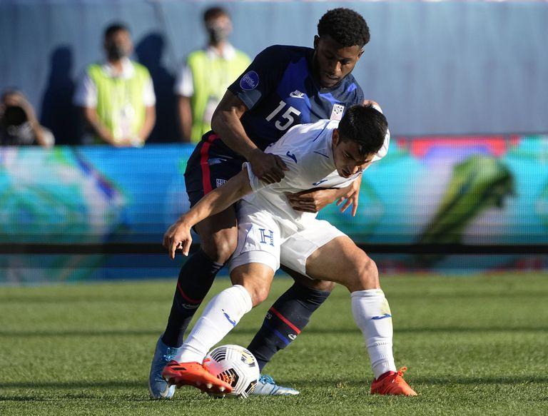 El zaguero de Estados Unidos Mark Mckenzie (15) marca al hondureño Diego Rodríguez en las semifinales de la Liga de Naciones de la CONCACAF, el jueves 3 de junio de 2021, en Denver. (AP Foto/Jack Dempsey)