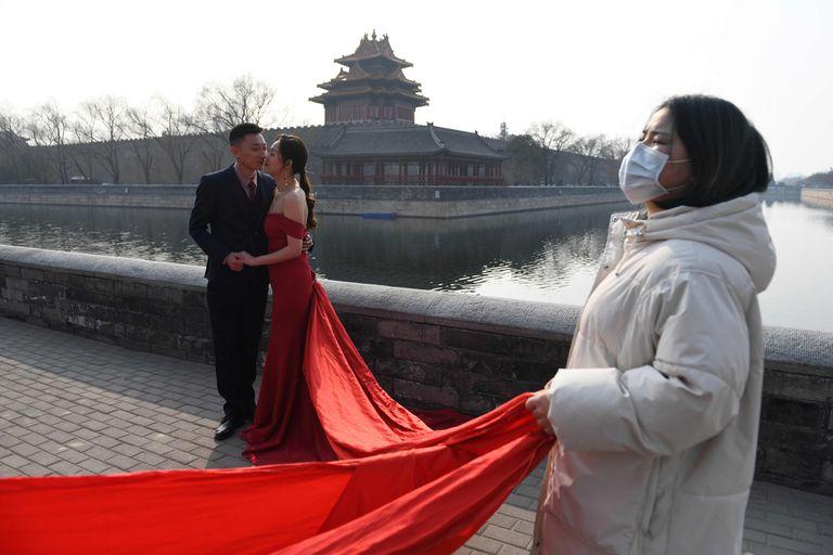 Una pareja se toma fotografías junto a la Ciudad Prohibida