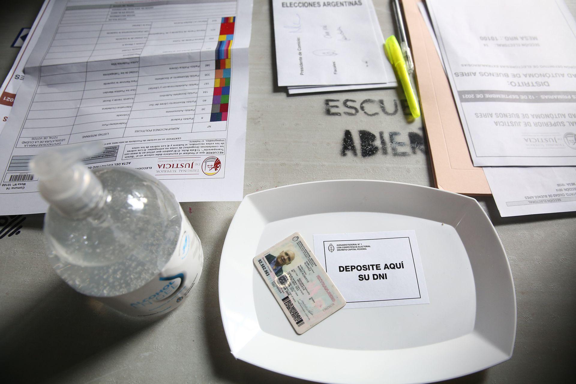 Alcohol en gel y bandeja de plástico para el documento en una de las mesas de la escuela de Juncal 3131