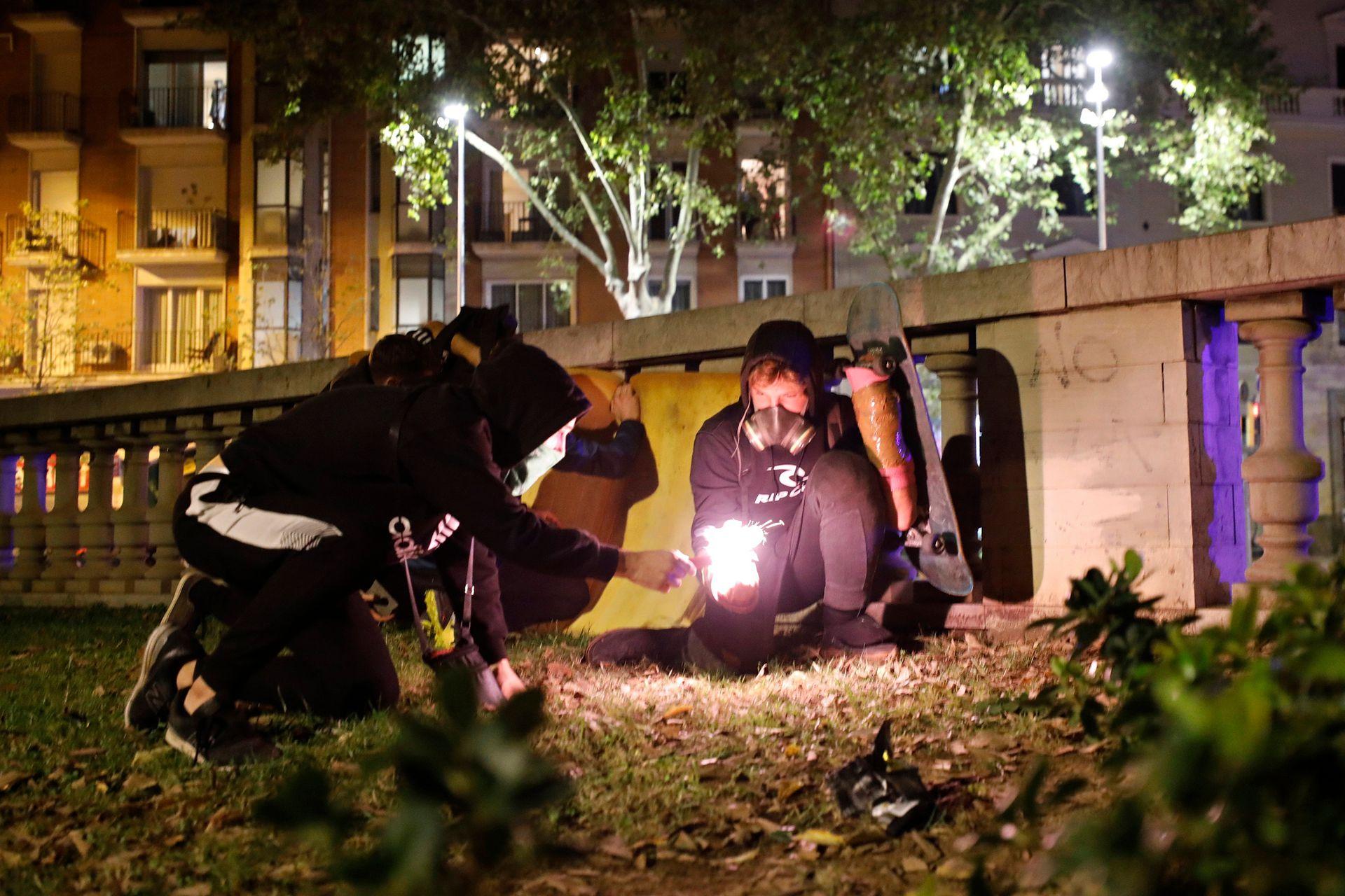 Manifestantes encienden una bengala para arrojarla a la policía