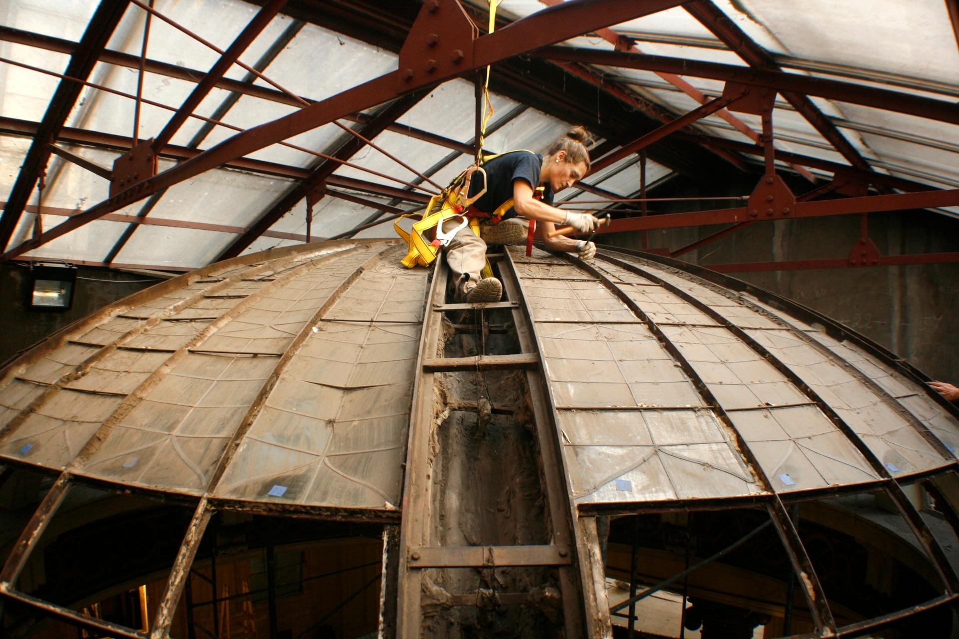 Paula Farina Ruiz en plenas tareas de restauración de la cúpula del ex café Retiro en la estación del ferrocarril Retiro Mitre.
