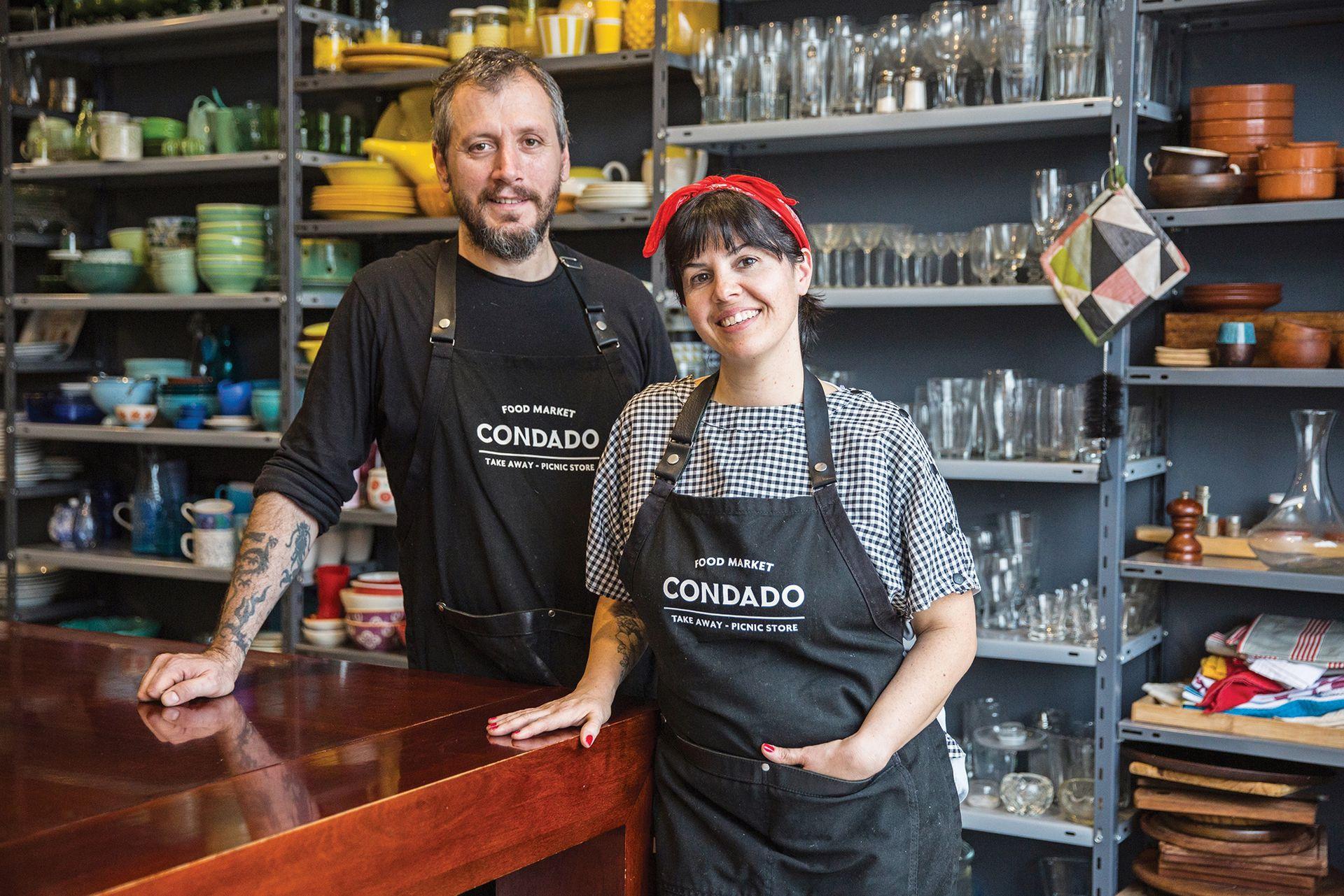 Juan de Francesco y Mariana Santos posan en el sector de arriba de la tienda, en el que tienen vajilla de utilería y una gran mesa para eventos.