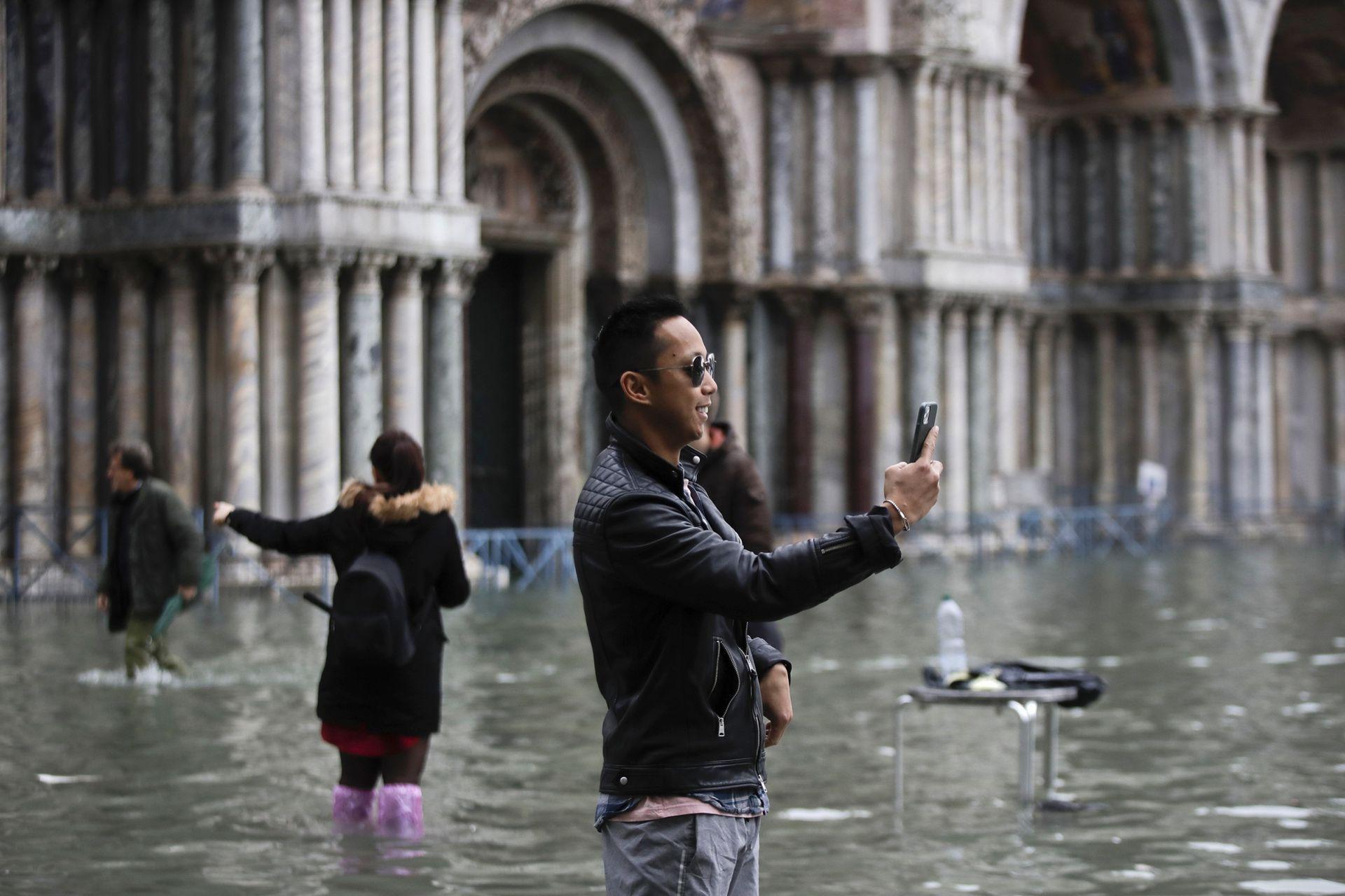 Los turistas toman fotos en una inundada
