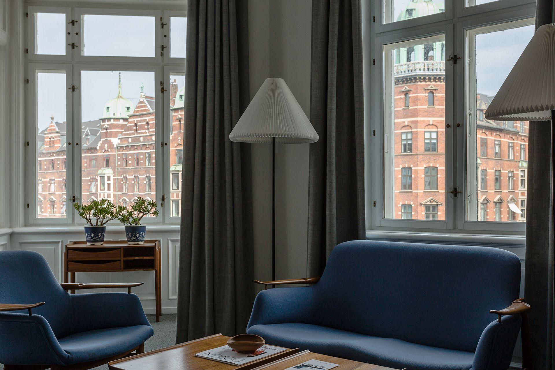 El equipamiento: sillón 'FJ 01', sofá 'FJ 02', la mesa con sus característicos cajones sin tirantes, enmarcadas por elegantes cortinados y moquette grises.