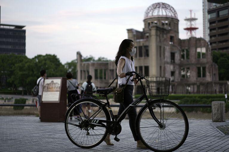 """Una mujer avanza frente a la """"Cúpula de la bomba atómica"""", en vísperas de la conmemoración del bombardeo del 6 de agosto de 1945"""