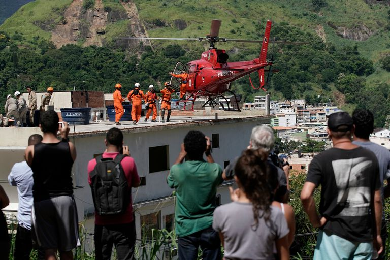 Residentes observan un helicóptero de rescate que transporta una mujer herida en el barrio de Muzema, en Río de Janeiro