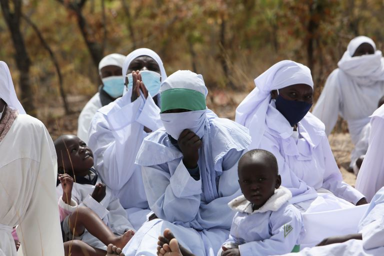 Miembros de la Iglesia Crisitana Apostólica participan en un servicio al aire libre en las afueras de Harare, la capital de Zimbabue, el 19 de septiembre del 2021. La iglesia es una de las más escépticas respecto a las vacunas contra el COVID-19. (AP Photo/Tsvangirayi Mukwazhi)