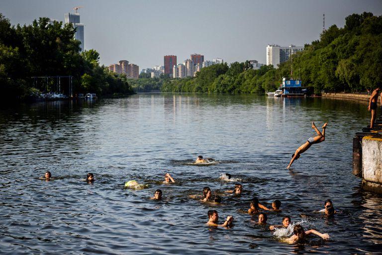 Jóvenes rusos se refrescan en el río Moscova, en la capital