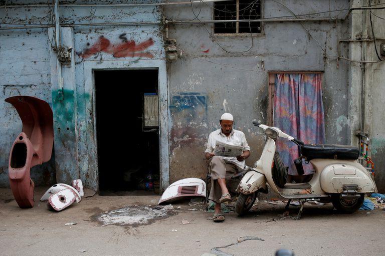 Amin, que pinta piezas de Vespa reparadas, lee un periódico afuera de su taller en Karachi, Pakistán