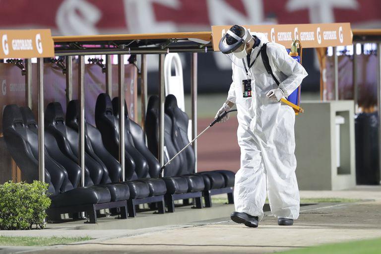 Un trabajador desinfecta un banco de suplentes en el estadio Morumbi para evitar la propagación del COVID-19.