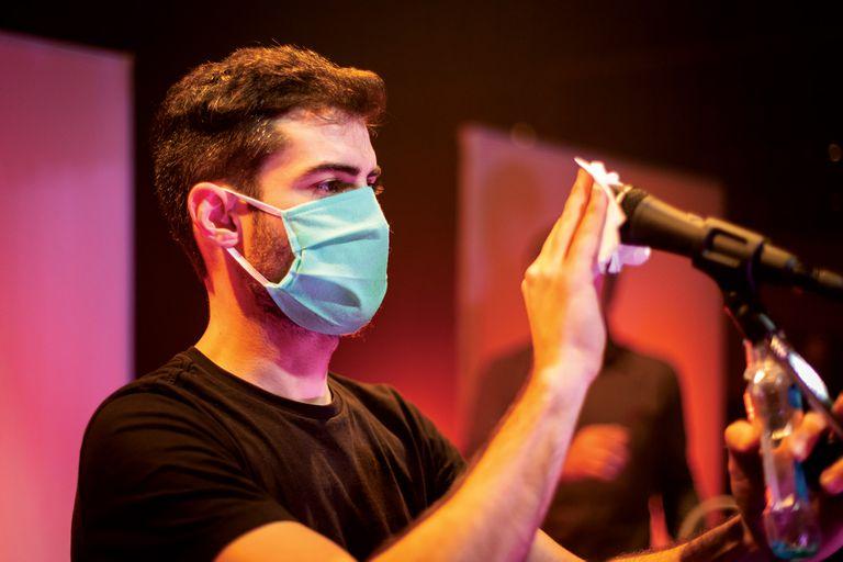 El stage de Kevin Johansen sanitiza uno de los micrófonos que se van a usar durante el recital