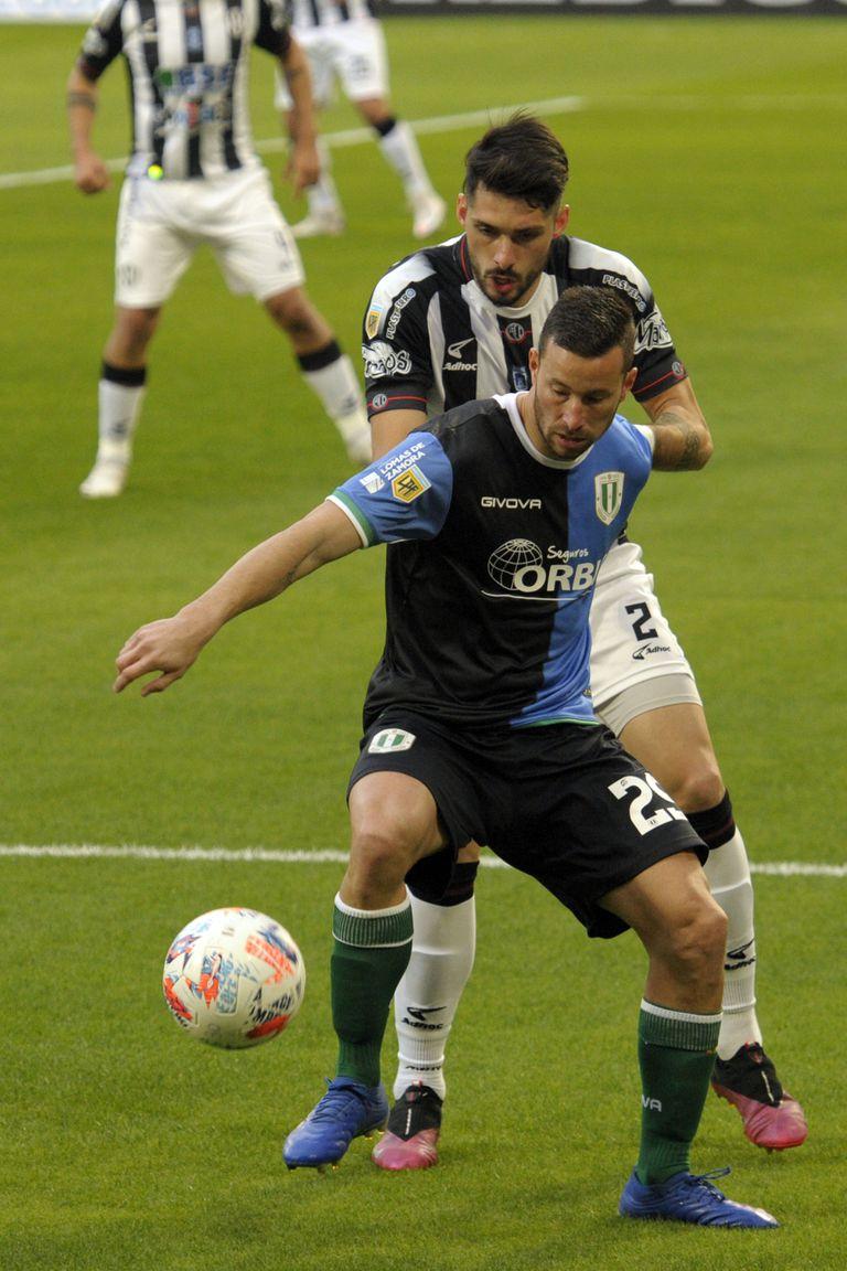 Luciano Pons aguanta la marca de Federico Andueza; una escena de Banfield y Central Córdoba, por la primera fecha del Torneo 2021