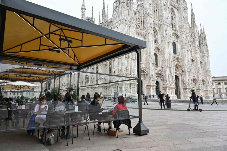 People have a lunch at a terrace in Duomo square on April 26, 2021 in central Milan. - Bars, restaurants, cinemas and concert halls will partially reopen across Italy Monday in a boost for coronavirus-hit businesses, as parliament debates the government's 220-billion-euro ($266-billion) EU-funded recovery plan. After months of stop-start restrictions imposed to manage its second and third waves of Covid-19, Italy hopes this latest easing will mark the start of something like a normal summer. (Photo by Miguel MEDINA / AFP)